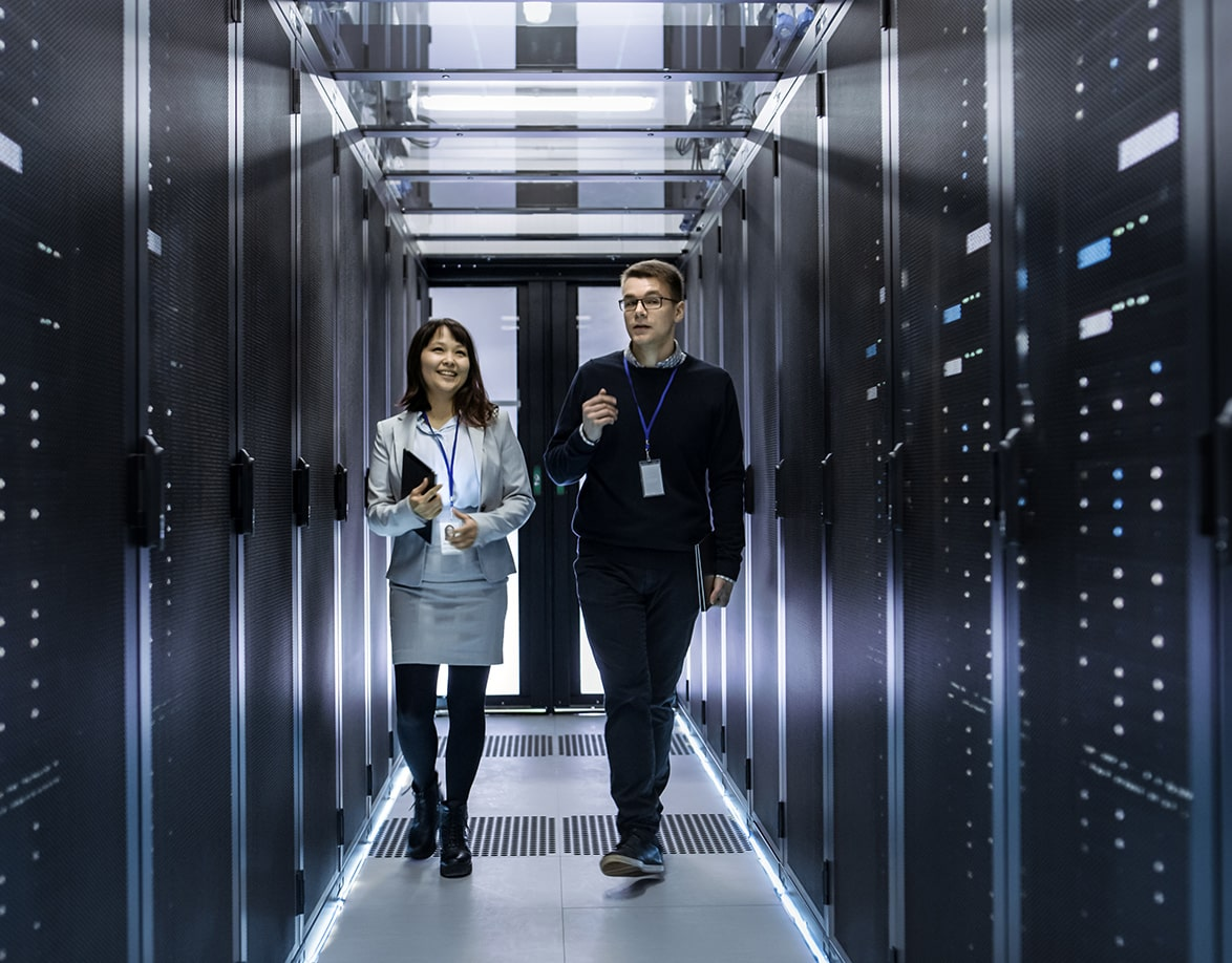 Two smiling co-workers in data center